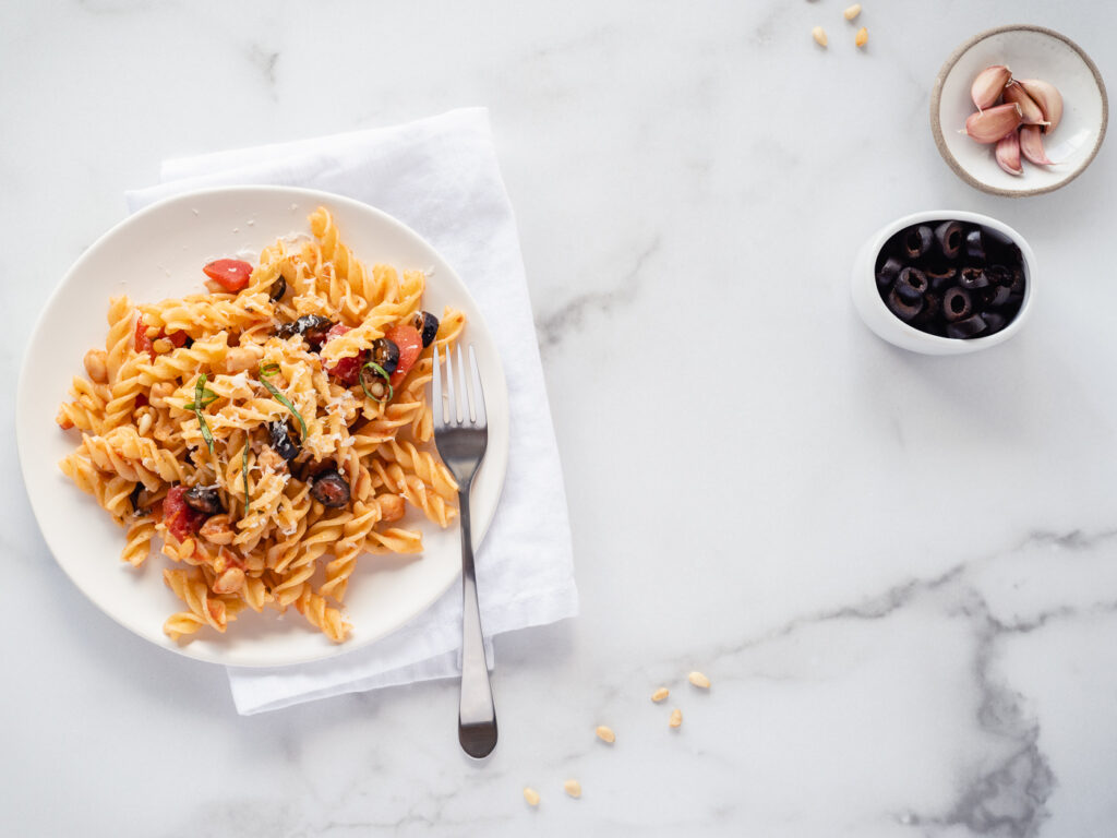 Plate of pasta with a fork and two small bowls of garlic and olives