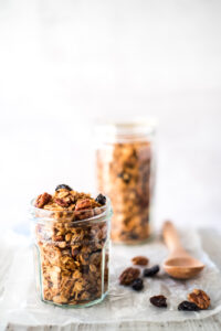 Two jars of granola on a board with a spoon