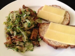 Plate with tofu and brussels sprouts next to bread with cheese