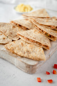 Quesadillas lined up on a cutting board