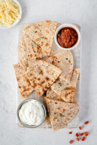 Top down view of a cutting board covered with quesadilla triangles