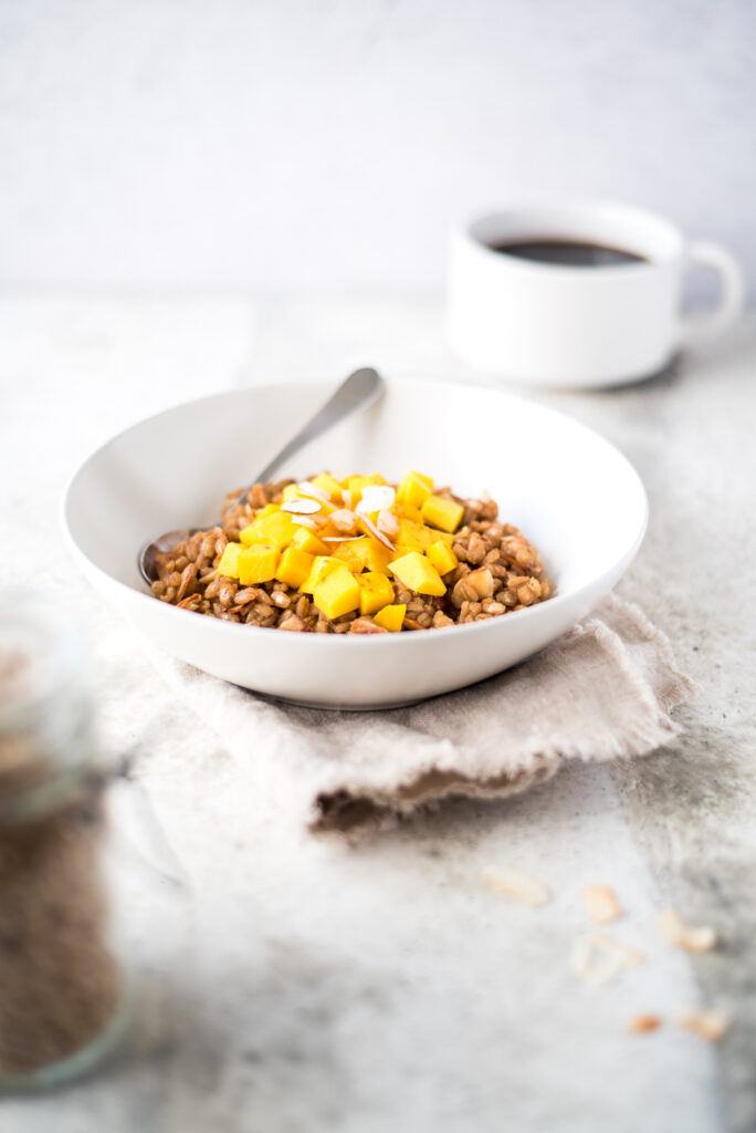 Bowl of hot cereal with mango next to a cup of coffee