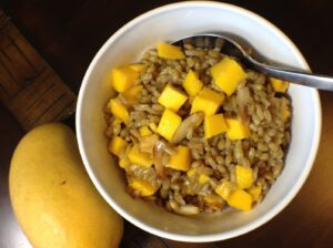 White bowl filled with hot cereal and mango chunks next to a whole mango