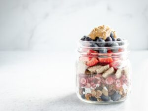 mason jar filled with coconut, fruit, cereal and peanut butter