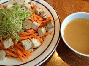 Bowl of tofu and veggies next to a bowl of sauce