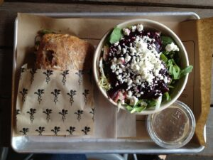 Sandwich and salad on a metal lunch tray