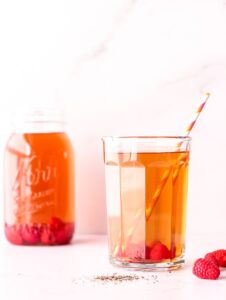 Cup of iced tea with raspberries and a straw in front of a mason jar of iced tea
