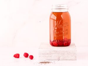 Mason jar filled with iced tea and raspberries on a white background