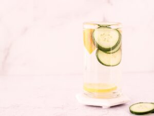 Glass of water with lemon, cucumber and orange slices in it