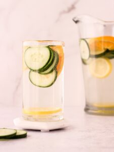 Glass of water with fruit and veggie slices in it in front of a pitcher of water