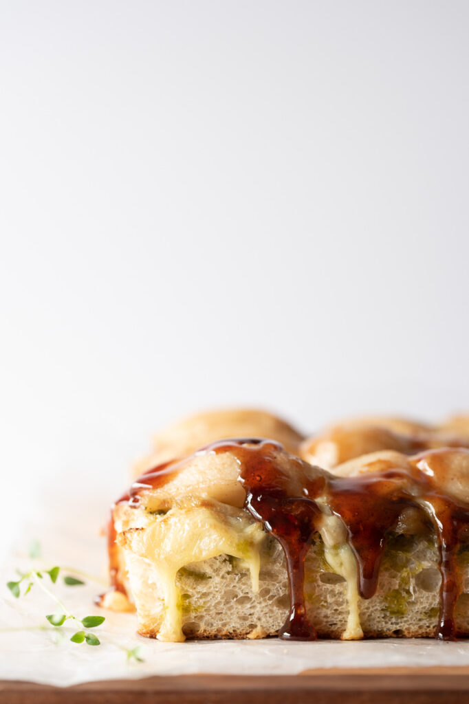 Close up of a piece of focaccia topped with cheese and pears