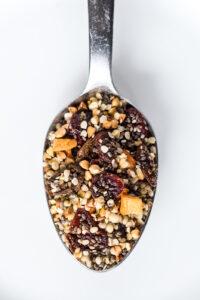 Close up on spoon full of seeds and dried fruit cereal