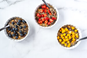 Three bowls of seeds and dried fruit cereal topped with fresh fruit