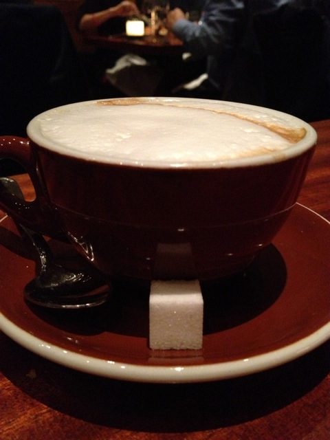 Cup of cappuccino with a sugar cube and spoon