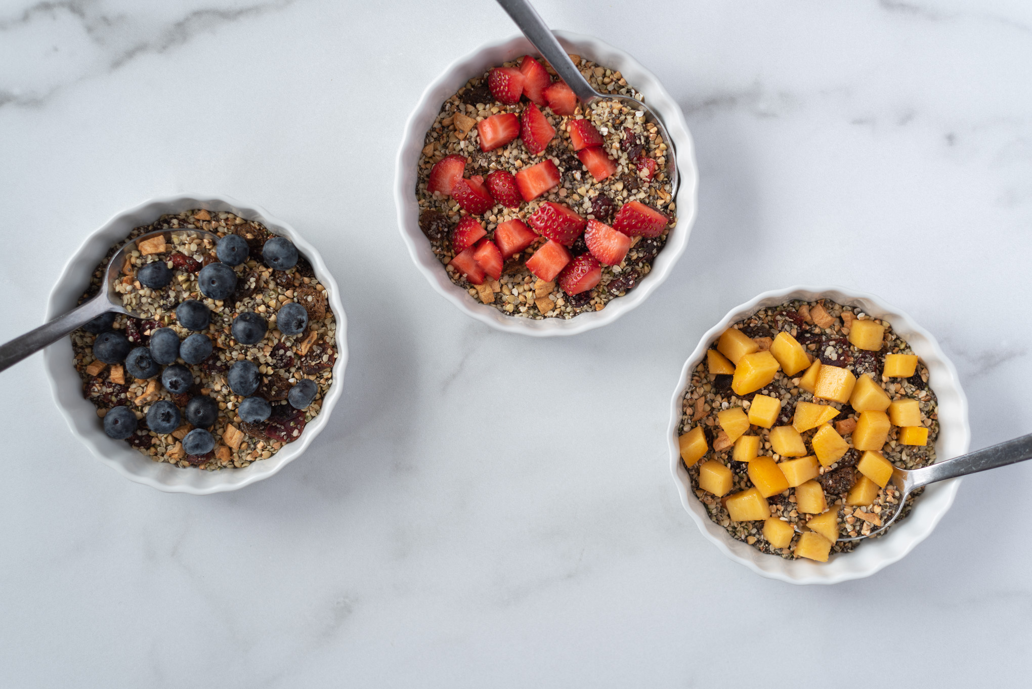 Three bowls of cereal with fruit