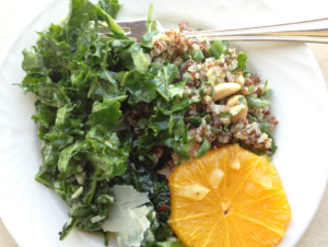 Plate with kale salad and an orange slice