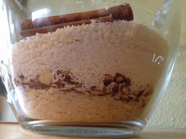 Rice, almonds, coconut and cinnamon sticks layered in a glass measuring cup