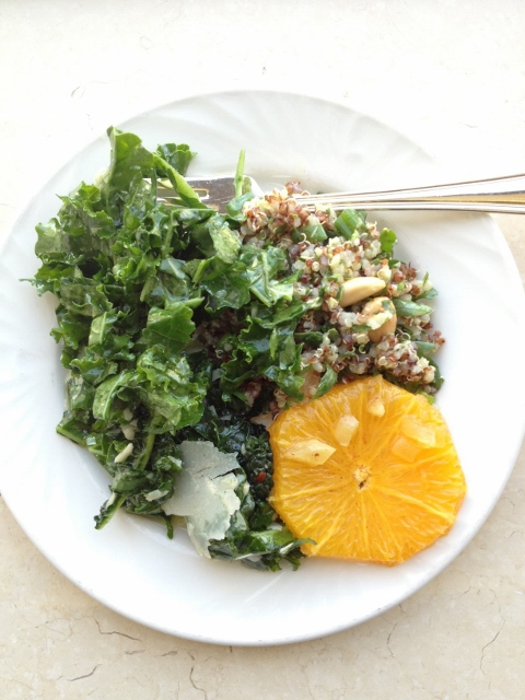 Kale salad, tabbouleh and sliced oranges on a plate