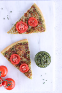 Top down view of 2 slices of pizza on a marble cutting board with a jar of pesto