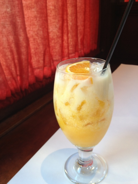 Orange and vanilla drink in a stemmed glass on the table