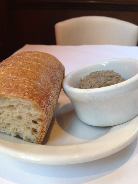 Small loaf of bread on plate with a cup of lentil spread