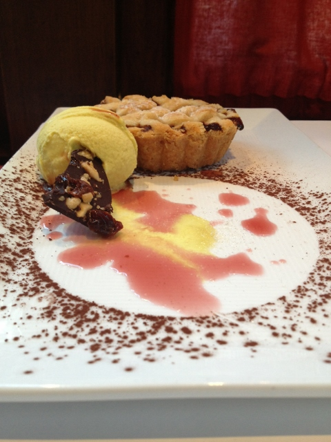 Small cherry pie with ice cream on a plate