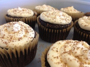6 chocolate cupcakes with white frosting and chocolate shavings