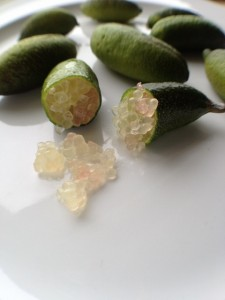Several small limes on a plate, one cut in half with pearls spilling out