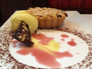Ice cream and a small pie on a beautifully decorated dessert plate