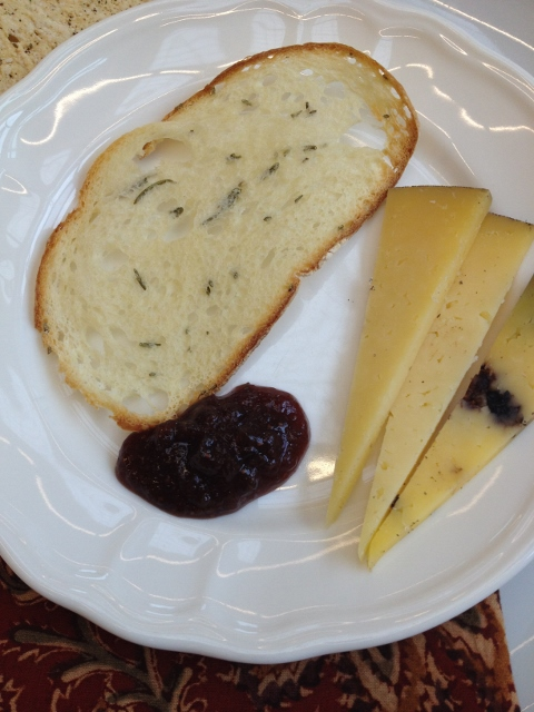 Bread, sliced cheese and a blob of jam on a white plate