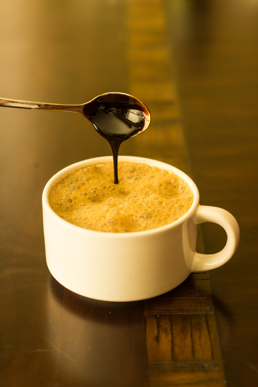 Cup of hot soymilk with molasses being drizzled in from a spoon
