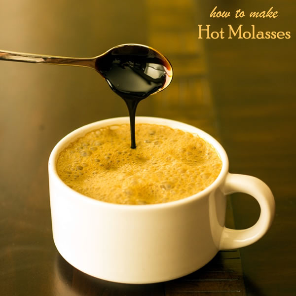 Cup of soymilk with molasses dripping in from a spoon