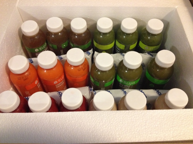 18 bottles of Suja juice in box
