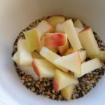 Buckwheat and chia cereal in bowl topped with chopped apples