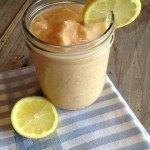 Peach smoothie in mason jar with sliced lemon garnish