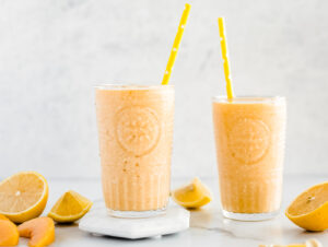 Two glasses of peach smoothie with cut lemons and peaches