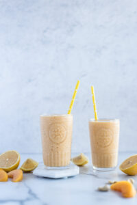 Two glasses full of peach smoothie