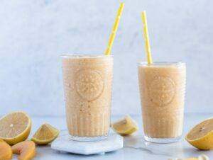 Two glasses full of peach smoothie with cut up lemons