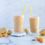 Two glasses of peach smoothie surrounded by peaches and lemon slices