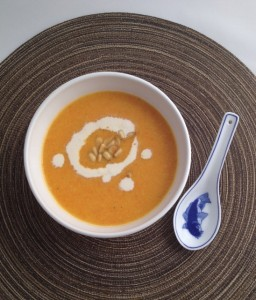 Bowl of Creamy Roasted Carrot Soup topped with pine nuts