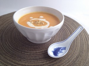 Bowl of Creamy Roasted Carrot Soup garnished with pine nuts