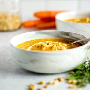 Bowl of carrot soup, pine nuts, bunch of carrots