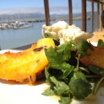 Grilled peaches served with cheese, honey and watercress
