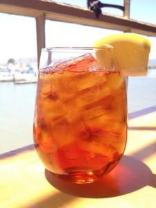 Refreshing glass of mango iced tea garnished with lemon