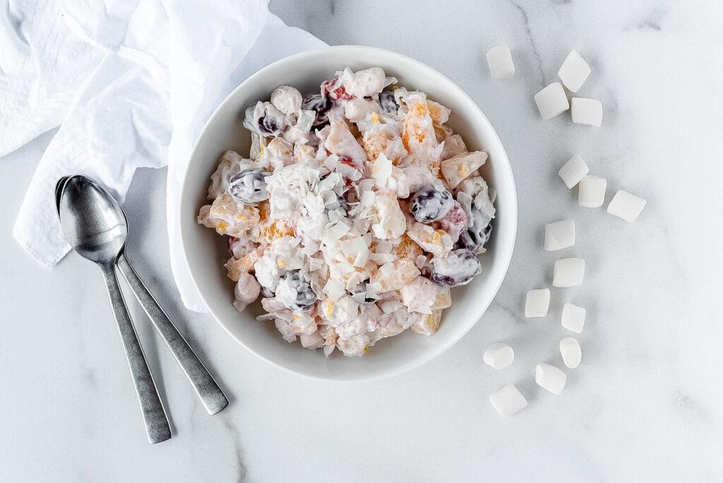 Top down view of a bowl of ambrosia next to some mini marshmallows