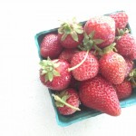 Overhead shot of a pint of strawberries in cardboard basket