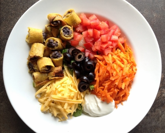Taquito Salad with olives, carrots, tomato, cheese and sour cream