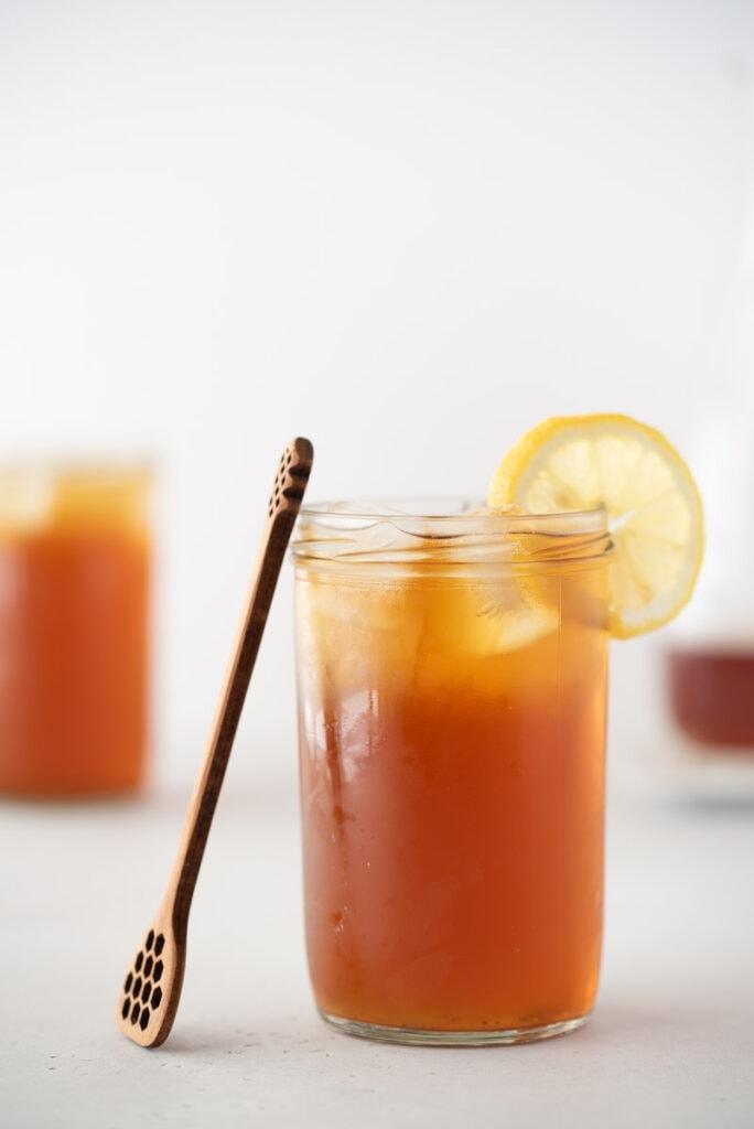 Glass of iced tea with lemon and a honey server