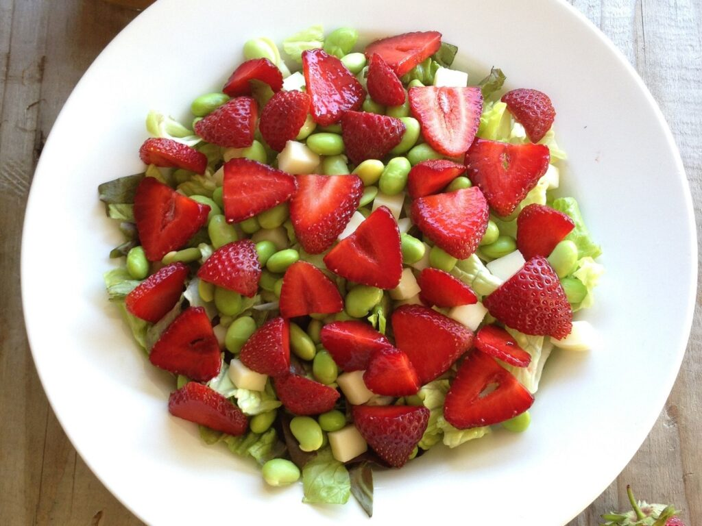 White bowl filled with lettuce, edamame beans and strawberries