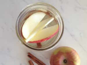 Top down view of canning jar with water and apple slices